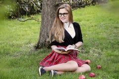 Libro de lectura de la muchacha/estudiante que lee un libro en parque/ Fotografía de archivo