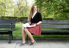 Libro de lectura de la muchacha/estudiante que lee un libro en parque/ fotos de archivo