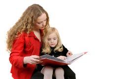 Libro de lectura de la muchacha a la hermana Fotografía de archivo libre de regalías