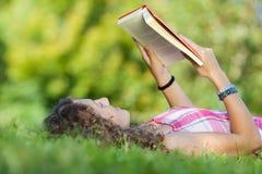 Libro de lectura de la muchacha mientras que miente en hierba Imagenes de archivo
