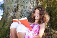 Libro de lectura de la muchacha mientras que se inclina en tronco de árbol Imágenes de archivo libres de regalías