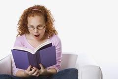 Libro de lectura de la muchacha que se sienta Imagen de archivo libre de regalías