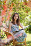 Libro de lectura de la muchacha que se sienta en la silla de mimbre al aire libre Imagenes de archivo