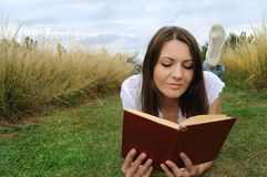 Libro de lectura de la mujer al aire libre Foto de archivo libre de regalías