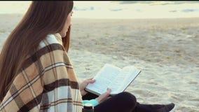 Libro de lectura de la mujer cerca del mar almacen de video