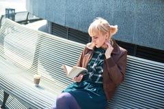 Libro de lectura de la mujer con la taza de café Fotos de archivo