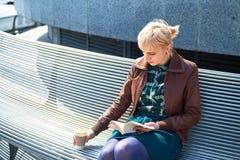 Libro de lectura de la mujer con la taza de café Fotografía de archivo libre de regalías