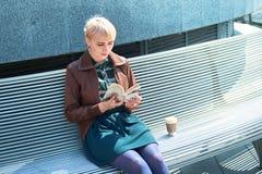 Libro de lectura de la mujer con la taza de café Fotos de archivo libres de regalías