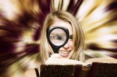 Libro de lectura de la mujer con una lupa Fotografía de archivo