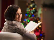 Libro de lectura de la mujer delante del árbol de navidad Fotos de archivo
