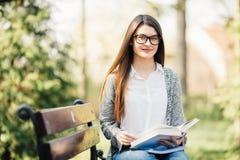 Libro de lectura de la mujer en banco de parque Imagenes de archivo