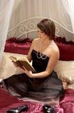 Libro de lectura de la mujer en cama Fotos de archivo libres de regalías