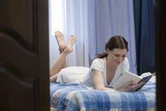 Libro de lectura de la mujer en cama Fotos de archivo