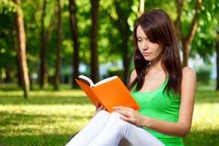 Libro de lectura de la mujer en el parque Imagen de archivo libre de regalías