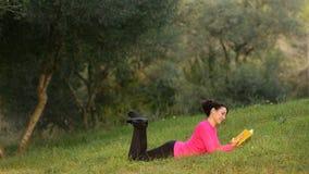 Libro de lectura de la mujer en el parque verde almacen de video