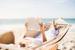Libro de lectura de la mujer en hamaca fotos de archivo