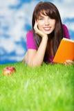 Libro de lectura de la mujer en la hierba. fondo del cielo Imágenes de archivo libres de regalías