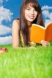 Libro de lectura de la mujer en la hierba. fondo del cielo Imagenes de archivo