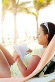 Libro de lectura de la mujer en la playa del Caribe Imagen de archivo libre de regalías