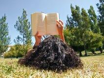 Libro de lectura de la mujer en parque Imágenes de archivo libres de regalías