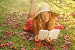 Libro de lectura de la mujer joven afuera Imágenes de archivo libres de regalías