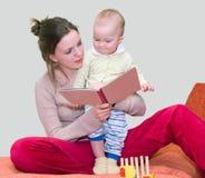 Libro de lectura de la mujer joven con el cabrito Imagen de archivo libre de regalías
