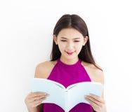 Libro de lectura de la mujer joven contra la pared blanca Imagen de archivo