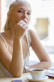 Libro de lectura de la mujer joven en el café Imagen de archivo libre de regalías