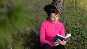 Libro de lectura de la mujer joven en el parque almacen de video