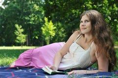 Libro de lectura de la mujer joven en parque Imagen de archivo libre de regalías