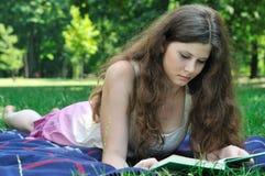 Libro de lectura de la mujer joven en parque Imágenes de archivo libres de regalías