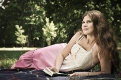Libro de lectura de la mujer joven en parque Imagen de archivo