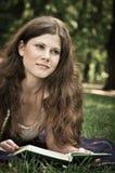 Libro de lectura de la mujer joven en parque Imagenes de archivo