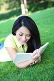 Libro de lectura de la mujer joven en parque Fotos de archivo