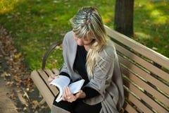 Libro de lectura de la mujer joven en un banco en un parque del otoño Imagen de archivo libre de regalías