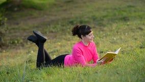 Libro de lectura de la mujer joven que miente en el prado almacen de metraje de vídeo