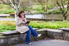 Libro de lectura de la mujer joven y café de consumición en parque de la primavera. Fotografía de archivo