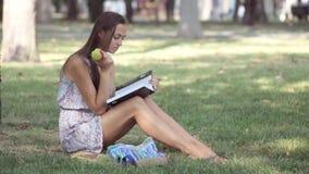 Libro de lectura de la mujer joven y manzana de la consumición en parque almacen de video