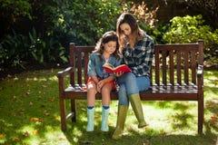 Libro de lectura de la mujer a la hija mientras que se sienta en banco de madera Imagenes de archivo