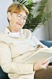 Libro de lectura de la mujer mayor Imagenes de archivo
