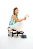 Libro de lectura de la mujer que se sienta en la pila de ellas Imagen de archivo libre de regalías