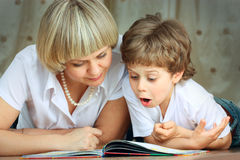 Libro de lectura de la mujer y del niño pequeño Imágenes de archivo libres de regalías