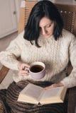Libro de lectura de la mujer y té de consumición Fotografía de archivo libre de regalías