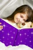 Libro de lectura de la niña con su oso del juguete Imagen de archivo