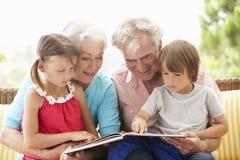 Libro de lectura de los abuelos y de los nietos en el jardín Seat Imagen de archivo