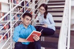 Libro de lectura de los estudiantes junto en la biblioteca Imagen de archivo libre de regalías