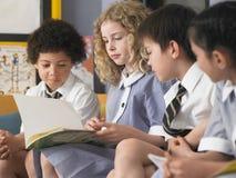 Libro de lectura de los estudiantes que se sienta en sala de clase Foto de archivo libre de regalías