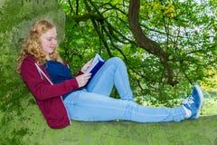 Libro de lectura de mentira de la muchacha en árbol verde Fotos de archivo