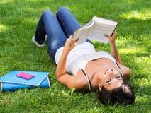 Libro de lectura de relajación de la chica joven Imagenes de archivo