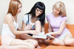 Libro de lectura de tres mujeres jovenes Imagen de archivo libre de regalías